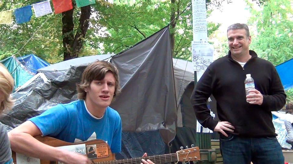 John Kuzmanich, Chairman of the Oregon TEA Party grooves along with Occupy Musician Trent from Hillsboro